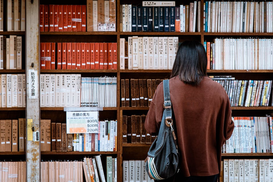 A man sitting in front of a book shelf